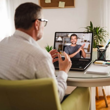 Deaf man talking using sign language on the laptop