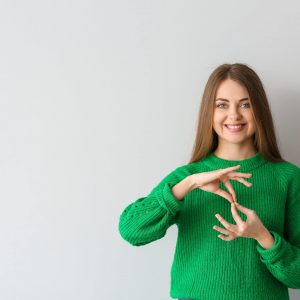 Young,Deaf,Mute,Woman,Using,Sign,Language,On,Light,Background